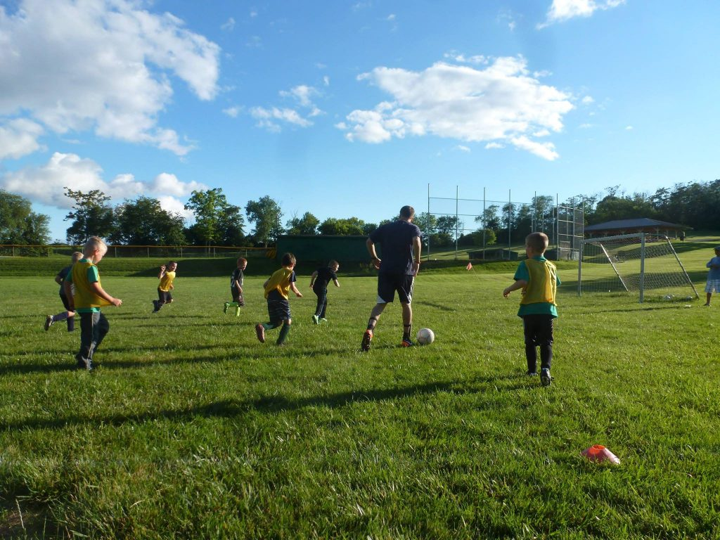 coach dribbling soccer ball with kids running alongside